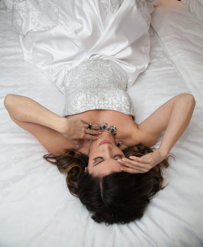 bride laying on the hotel bed in strapless wedding dress with jeweled necklace | Flowers by Festivities | Sheraton Hotel in Bloomington, MN | Hair by Hair by Heidi | Photo by Memories in Time Photography | Planned by Sixpence Events & Planning | Makeup by KMT beauty | Garters by Three Comforts | Jewelry by Style by Cia | Dress from Bridal Aisle | Model Katie Lietz