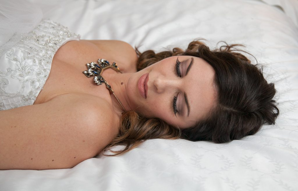 bride laying on the hotel bed with jewel necklace nad dramatic eye makeup, natural lip color | Flowers by Festivities | Sheraton Hotel in Bloomington, MN | Hair by Hair by Heidi | Photo by Memories in Time Photography | Planned by Sixpence Events & Planning | Makeup by KMT beauty | Garters by Three Comforts | Jewelry by Style by Cia | Dress from Bridal Aisle | Model Katie Lietz