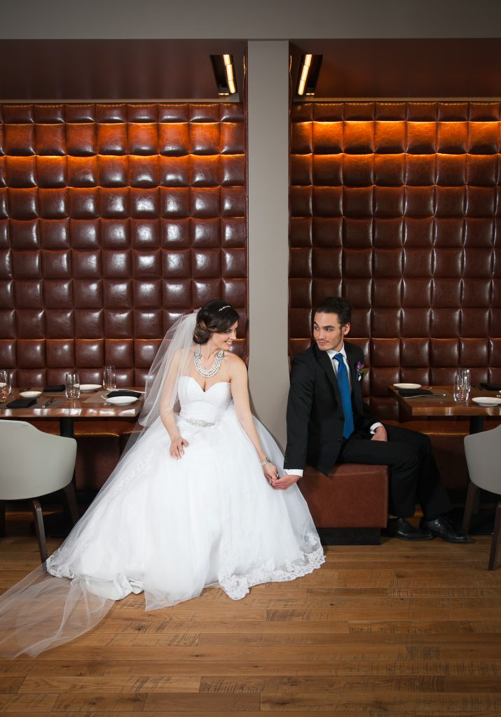bride and groom holding hands in leather restaurant booth, groom in blue tie | Flowers by Festivities | Sheraton Hotel in Bloomington, MN | Hair by Hair by Heidi | Photo by Memories in Time Photography | Planned by Sixpence Events & Planning | Makeup by KMT beauty | Garters by Three Comforts | Jewelry by Style by Cia | Dress from Bridal Aisle | Model Katie Lietz and Michael Senich