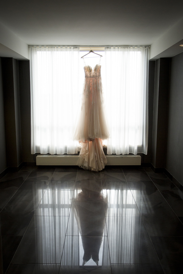 wedding dress hung in front of a window