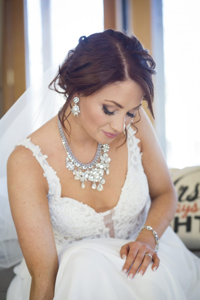bride with lots of jewelry and a mess low bun | Courtney June Photography | Minnesota wedding hair