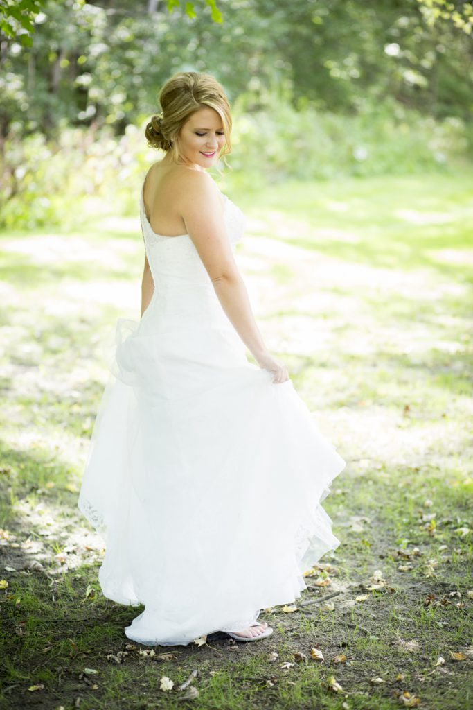 bridal low bun with side swept bangs and a one shoulder dress | Courtney June Photography | Minnesota wedding dress | Bride wearing thongs shoes