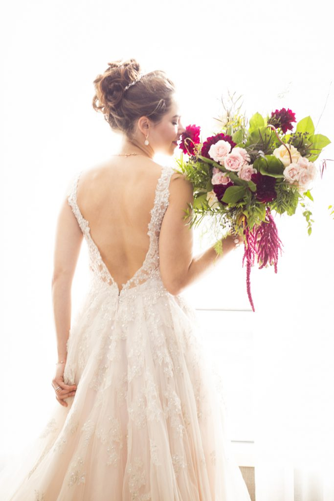 bride with a low v back with a crystal lace overlay and a high bun with a crystal hairpiece | Courtney June Photography
