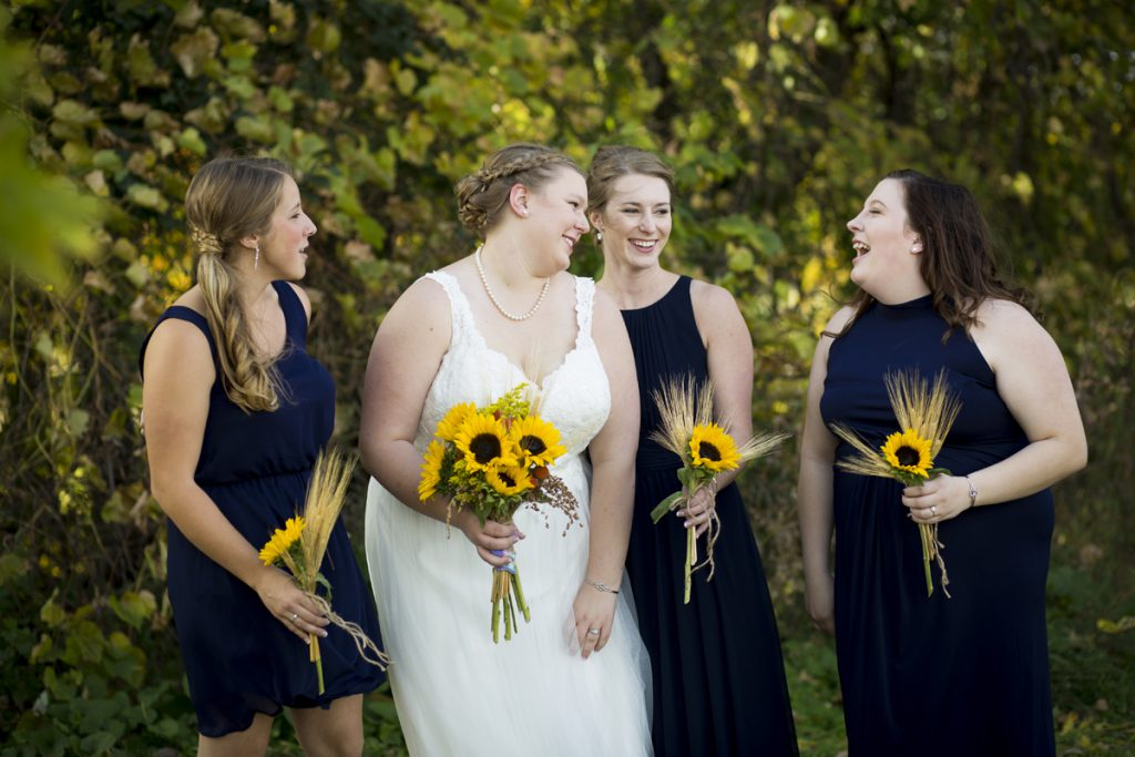 sunflower bouquets with wheat grass and short dark navy bridesmaids dresses | bride with a braid | Courtney June Minneapolis Photographer