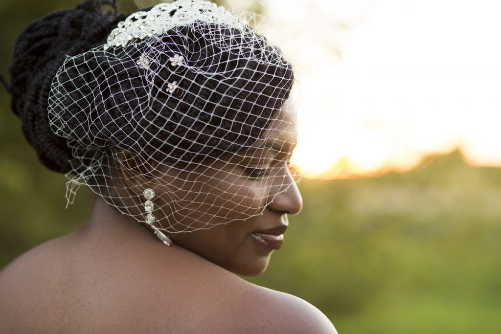 Beautiful dark skinned bride with braids in an updo and a birdcage veil and teardrop earrings | Courtney June Photography in Minneapolis
