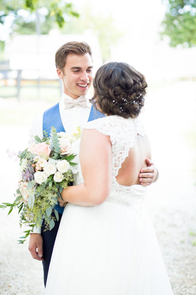 low bridal updo loosely braided with a hair piece and a key hole back | groom in a bright blue vest and pale pink bowtie | Courtney June Minnesota wedding photographer