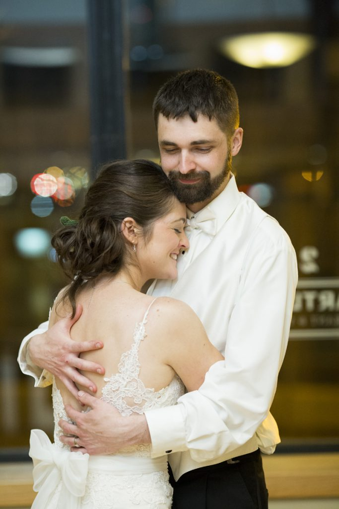 bridal low bun with a low back dress and a cute tulle bun | groom with a full beard and white on white bowtie | Courtney June wedding photographer in Minnesota
