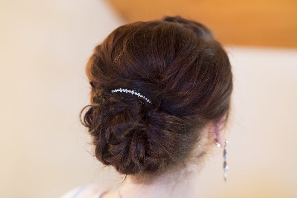 twisted bridal updo with a crystal pin and teardrop earrings | Courtney June Photography | Minnesota wedding hair