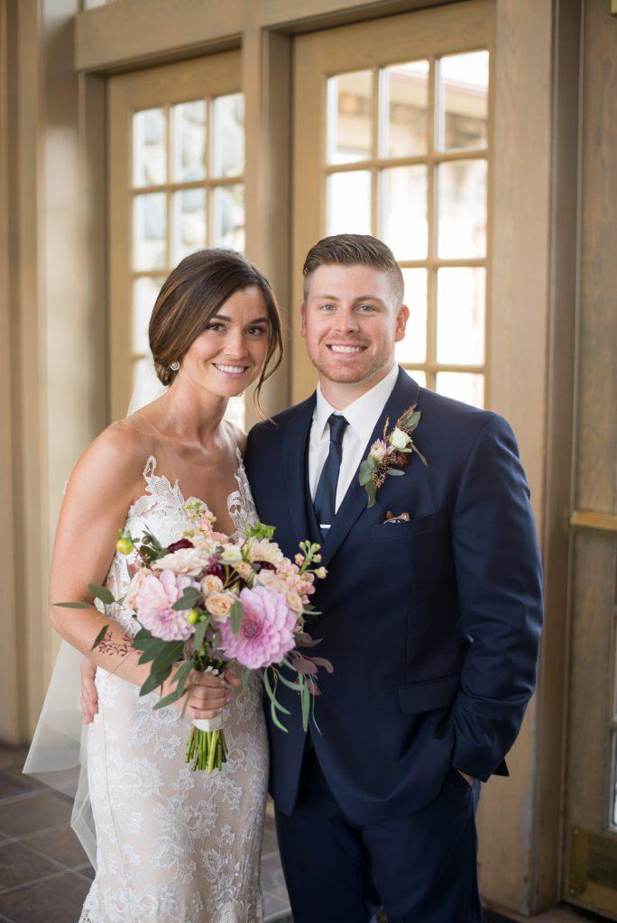 bride in lace low neckline wedding dress | groom in navy with navy tie