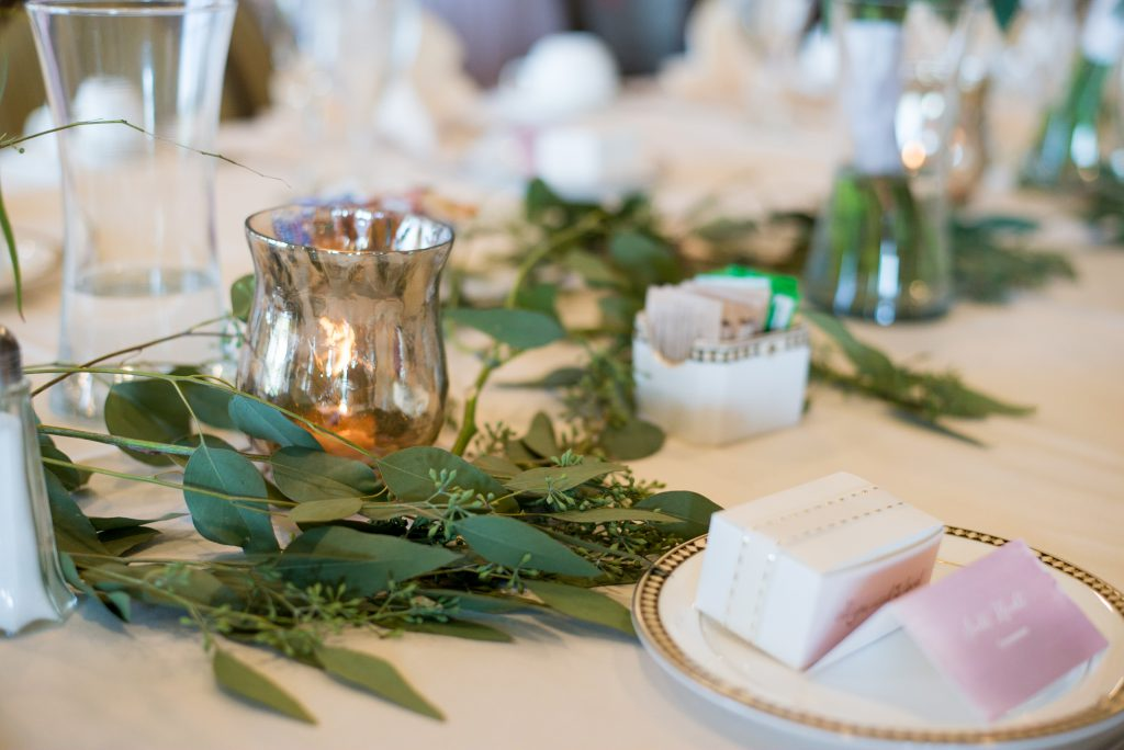 escort card on table with seeded eucalyptus and mercury votives