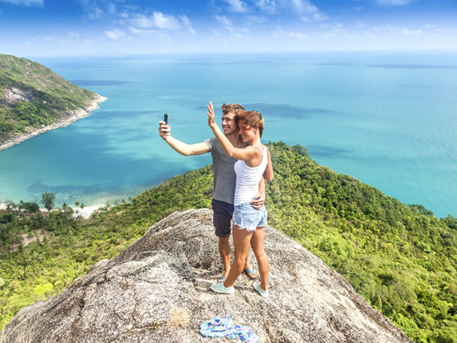 couple posing on cliff top etiquette of honeymoon gift list