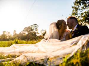 Bride and groom sit on grass Win a £500 Voucher and Photo Booth From Wright Wedding Photography