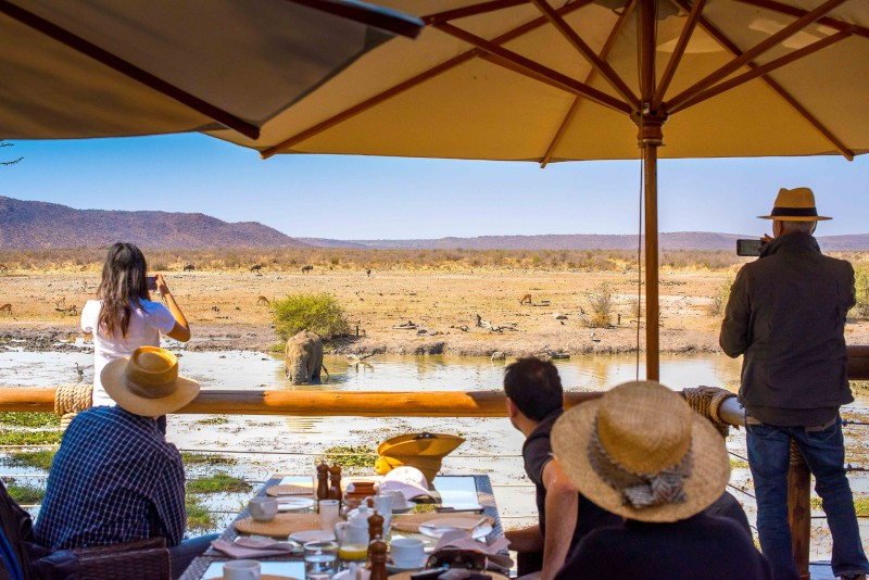 Tau lodge guests and waterhole